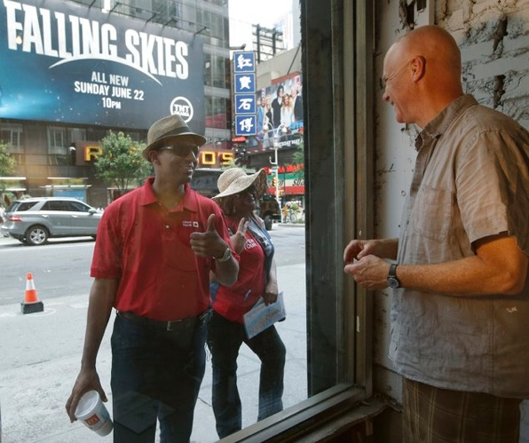 A bus tour supervisor and one of the tour company's employees pause in front of artist Tom Christopher, right, who has set up a temporary studio in the Brill Building with Andy Hammerstein in Times Square in New York, Wednesday, July 9, 2014. The artists, who are known for their New York cityscapes, have been working on the pop installation six hours a day since June 17. (AP Photo/Kathy Willens)